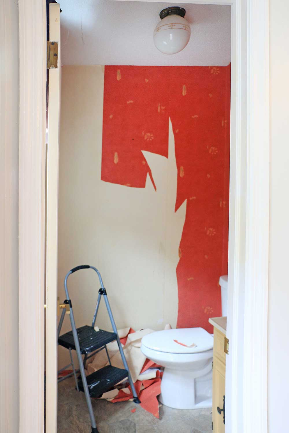 Powder-room-with-red-peeling-wallpaper