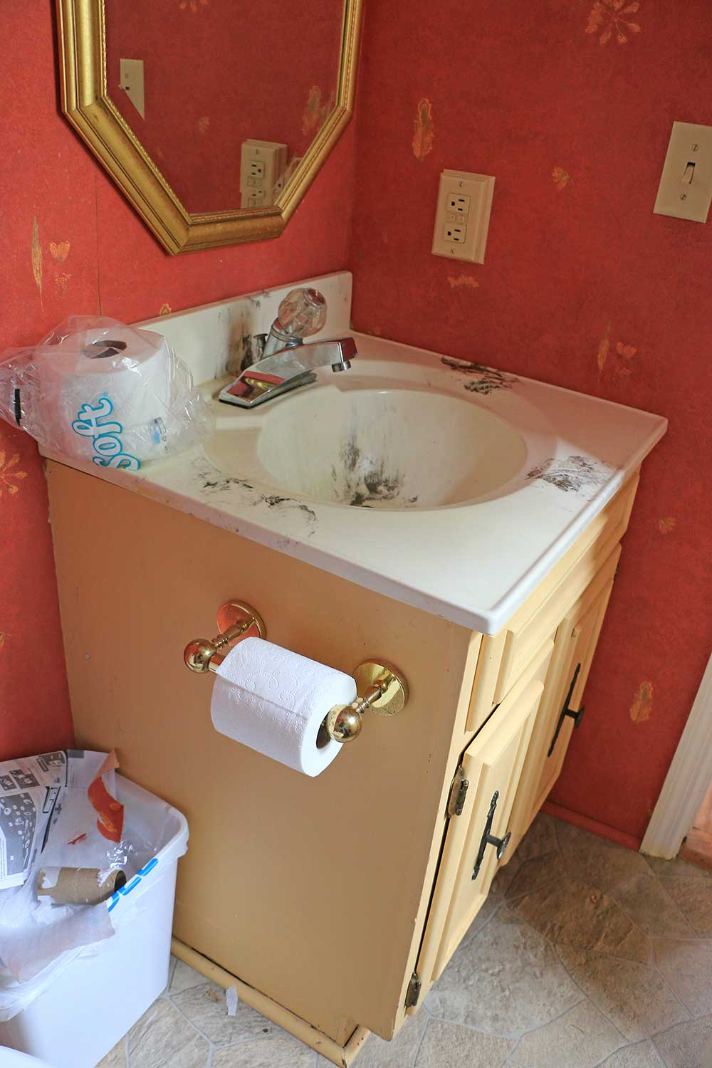 powder room makeover with yellow vanity and red wallpaper